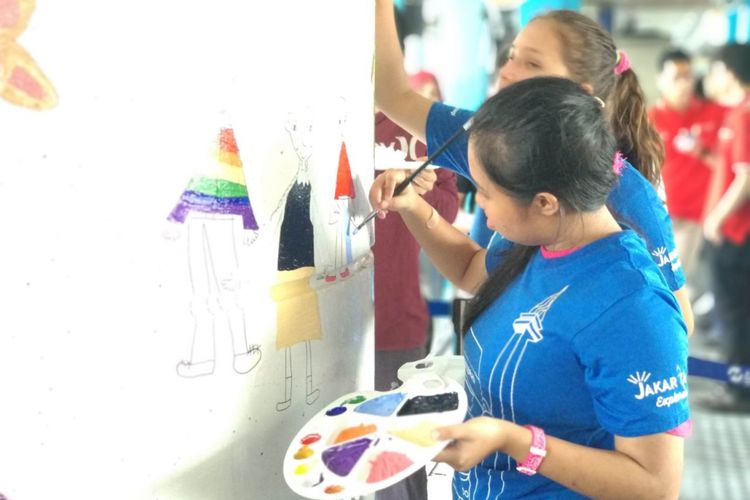 Anak-anak disabilitas dari yayasan Art Burt melukis dinding halte Transjakarta Kampung Melayu, Selasa (27/3/2018)