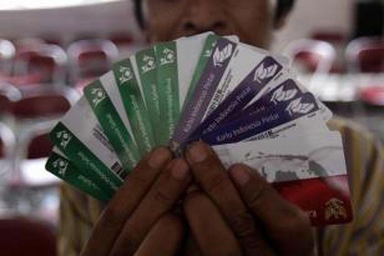 Warga menunjukkan Kartu Indonesia Sehat (KIS), Kartu Indonesia Pintar (KIP), dan Kartu Keluarga Sejahtera (KKS) di Kantor Pos Kampung Melayu, Jalan Jatinegara Barat, Jakarta Timur, Rabu (13/5/2015).