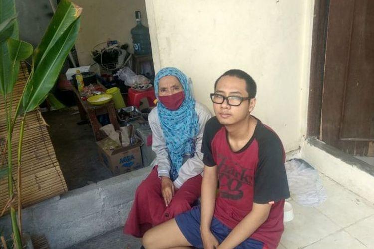 Endang Isnanik dan anaknya duduk di depan kamar kos yang disewa dengan harga Rp700 ribu per bulan di Denpasar, Bali. Air merendam tempat tidur menjadi ritual rutin di kala hujan datang