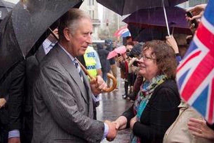 Pangeran Charles menyapa seorang warga kota Aucklan, Selandia Baru dalam kunjungannya ke negara itu.