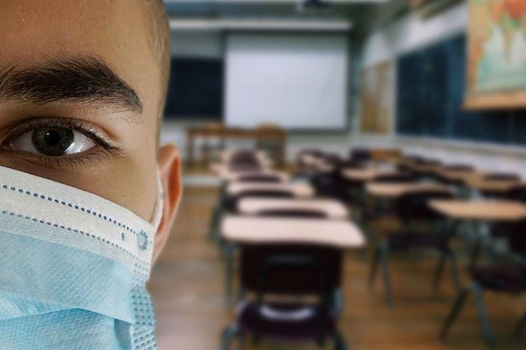 Ilustrasi siswa dalam kelas menggunakan masker.