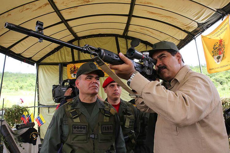 Presiden Venezuela Nicolas Maduro mencoba senapan buatan Rusia saat latihan militer bersama kedua negara di Carcas, Januari 2017 lalu.