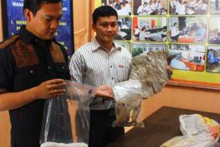 Kasat Reskrim AKP Hidayatullah (kanan) menunjukan barang bukti dari industri rumahan yang mengolah limbah kulit sapi bekas sepatu untuk dijadikan makanan, jenis kikil, dan cecek, di Kabupaten Cirebon, (04/09/2014).