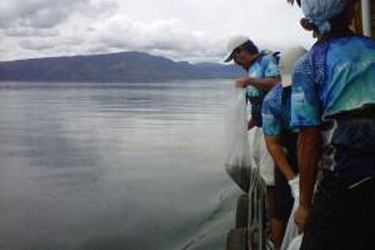 Peserta Jelajah Sepeda Sabang-Padang Kompas-PGN melakukan penebaran benih ikan nila di Danau Toba, Sumatera Utara, Sabtu (7/9/2013).