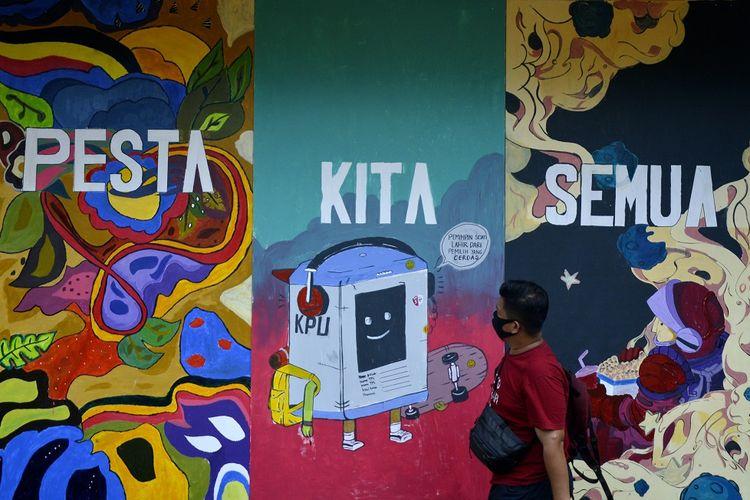 Warga melintas di dekat tembok bermural di Makassar, Sulawesi Selatan, Selasa (17/11/2020). Mural dengan tema Pilkada tersebut sebagai bentuk sosialisasi serta ajakan kepada masyarakat untuk menggunakan hak pilihnya pada pemilihan Wali Kota dan Wakil Wali Kota Makassar2020. ANTARA FOTO/Abriawan Abhe/foc.