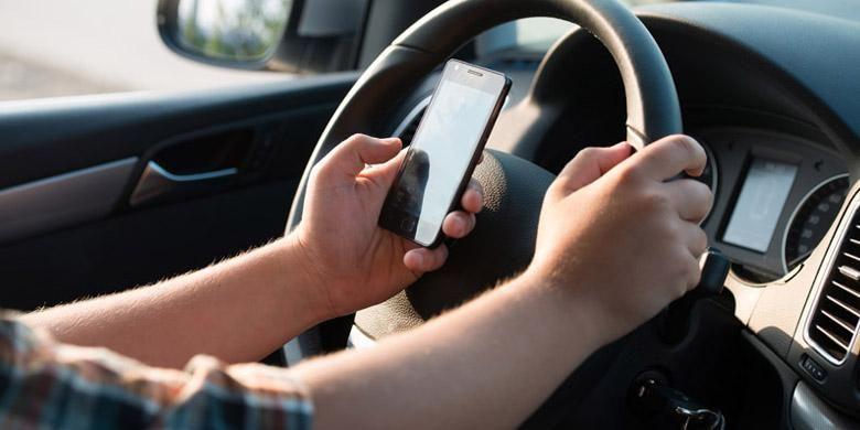 Ilustrasi berkendara sambil mengoperasikan ponsel.