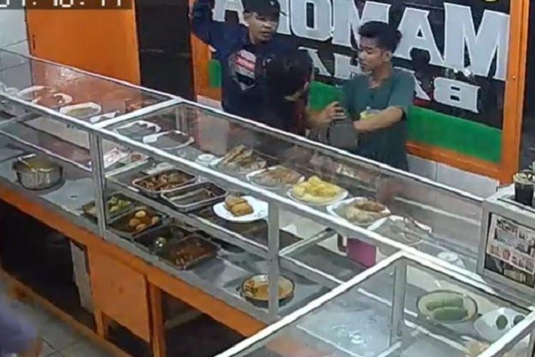 Komplotan penodong yang terdiri dari tiga pria merampas dompet dan ponsel seorang pria yang sedang  makan di sebuah rumah makan di Petukangan Utara, Pesanggrahan, Jakarta Selatan, Senin (20/1/2020) malam. Dalam gambar tampak dua dari mereka sedang mengancam korban yang membelakangi kamera.