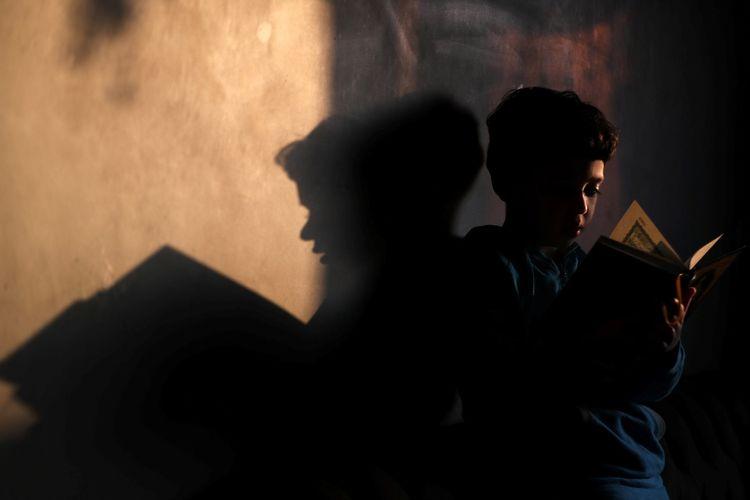 Seorang anak lelaki membaca Al-Quran setelah shalat subuh pada bulan suci Ramadhan di Kairo, Mesir, di tengah upaya kuat negara itu menekan laju penularan virus corona (Covid-19), Minggu (26/4/2020). Di tengah pandemi Covid-19, Ramadhan tahun ini berlangsung dengan suasana sepi, berbeda dengan tahun-tahun sebelumnya.