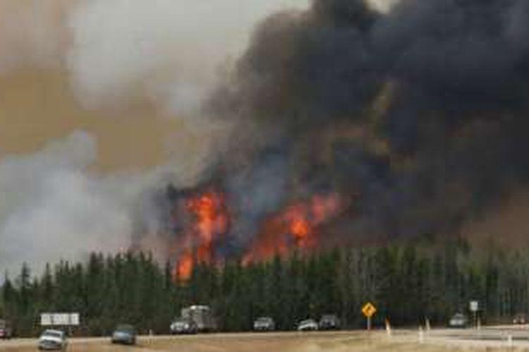 Konvoi terdiri dari 1.500 kendaraan terpaksa dihentikan untuk sementara, akibat jilatan api setinggi 60 meter yang melalap jalan di wilayah Fort McMurray, di Provinsi Alberta, Kanada.