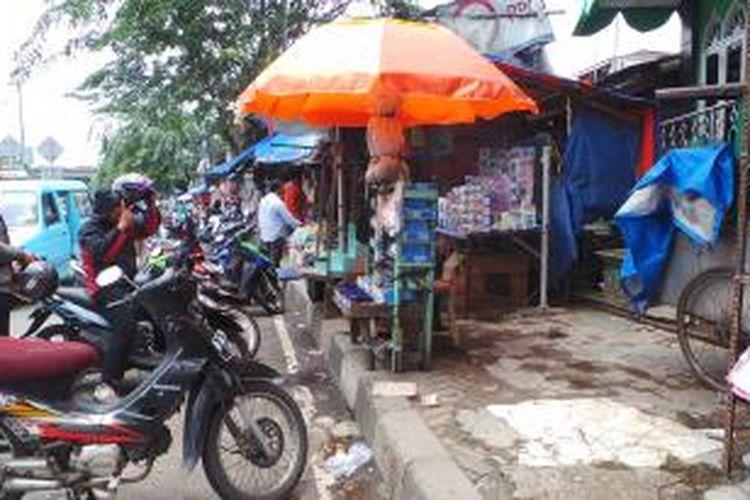 Para pedagang kaki lima yang sempat berjualan di tempat relokasi Pasar Cipinang Besar Selatan kembali berjualan di trotoar Jalan Basuki Rahmat, Jakarta Timur,  Senin (24/2/2014). Pedagang mengaku merugi karena lapak mereka di pasar itu sepi pembeli.