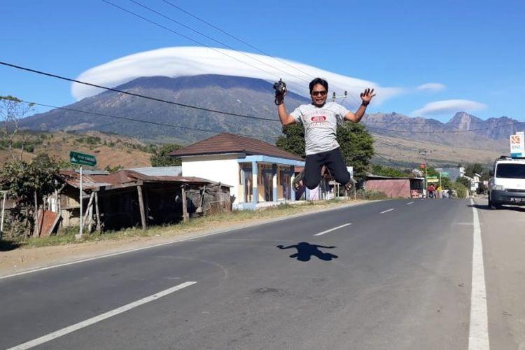 Warga menyaksikan fenomena topi awan yang melingkari puncak hingga lereng Gunung Rinjani, di Lombok, NTB, Rabu (17/7/2019.