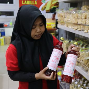 Seorang pelayan di pusat oleh-oleh DaudCirebon, sedang menunjukan Sirup Tjampolay yang merupakan minuman khas Cirebon, Selasa (5/8/2017).