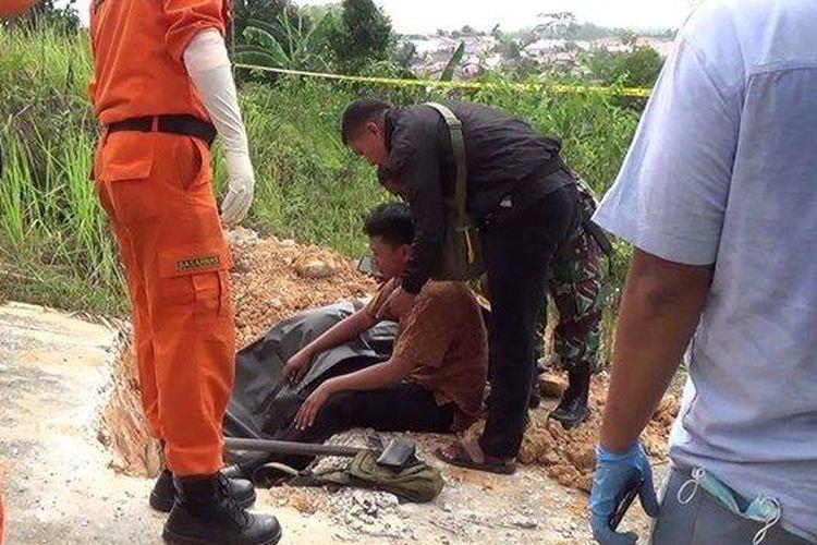 Jasad Korban (ditutupi terpal) tergeletak di dekat galian tanah di ujung pengecoran jalan di kawasan Perumahan Graha Indah Balikpapan Utara sebelum kemudian dievakuasi petugas.