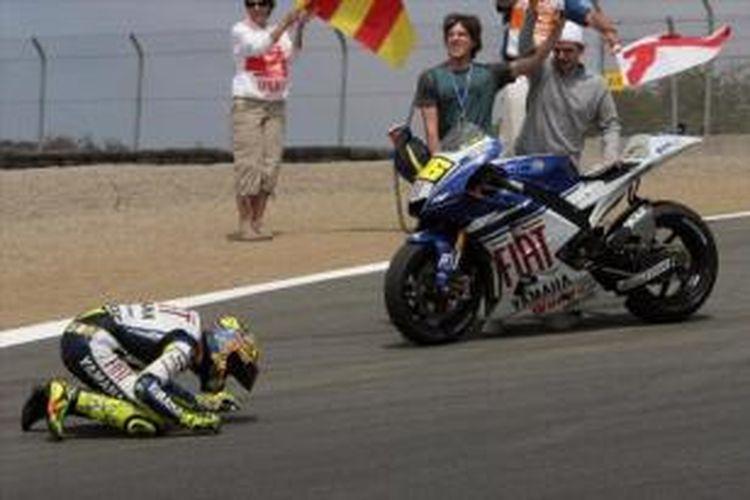 Pebalap Yamaha, Valentino Rossi mencium aspal Sirkuit Lagun Seca, setelah berhasil finis pada balapan GP Amerika Serikat, 20 Juli 2008.