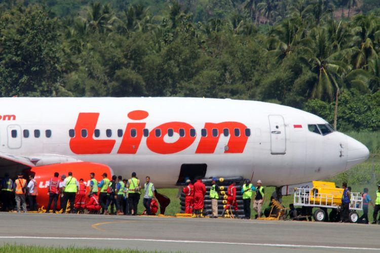 Sejumlah petugas berusaha memindahkan pesawat Lion Air yang tergelincir di Bandara Jalaluddin Tantu Gorontalo. Upaya mereka belum menemukan keberhasilan