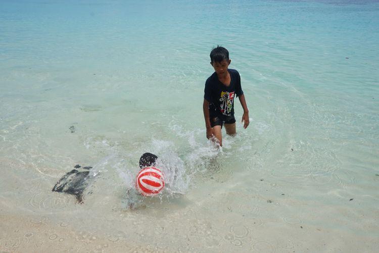 Seorang anak sedang bermain bola di pantai Wambar Fakfak Papua Barat