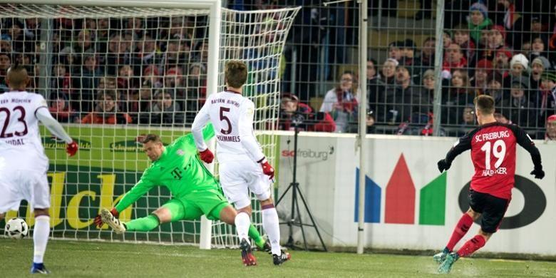 Gelandang Freiburg, Janik Haberer (kanan), mencetak gol ke gawang Bayern Muenchen yang dikawal Manuel Neuer, dalam pertandingan Bundesliga di Freiburg, Jerman, Minggu (20/1/2017).