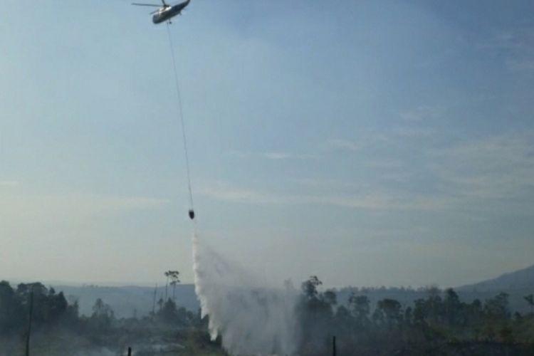 Helikopter water bombing melakukan penyiraman api pada kebakaran hutan lindung Bukit Suligi di Desa Kumain, Kecamatan Tandun, Kabupaten Rohul, Riau, Kamis (22/7/2021).