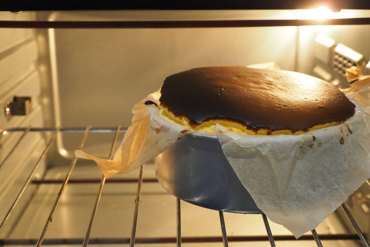 Ilustrasi Basque cheesecake sedang dipanggang. Basque cheesecake adalah kue keju khas Spanyol.