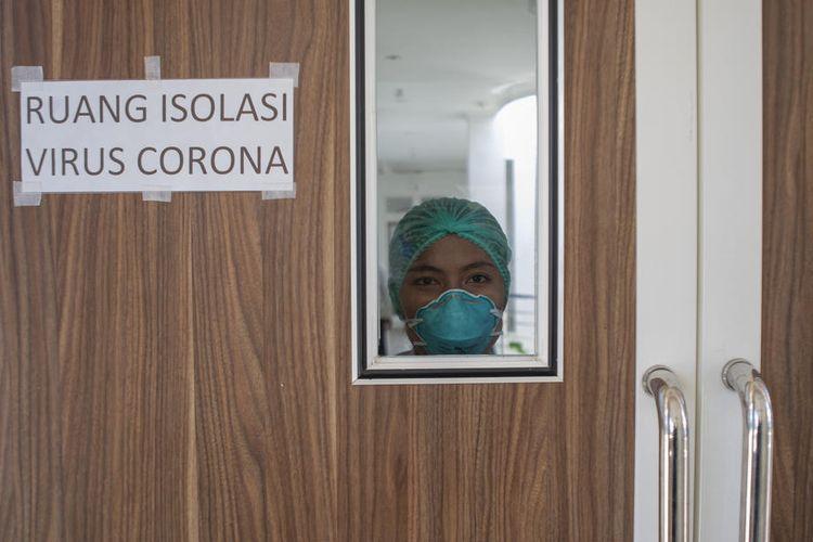 Seorang perawat Indonesia melihat melalui jendela kaca dari ruang isolasi untuk pasien yang terinfeksi virus corona, di Rumah Sakit Undata di Palu, Sulawesi Tengah, Indonesia, 3 Maret 2020. Rumah sakit di seluruh negeri sedang bersiap-siap untuk menghadapi kemungkinan wabah setelah dua kasus pertama virus corona. EPA-EFE/OPAN BUSTAN