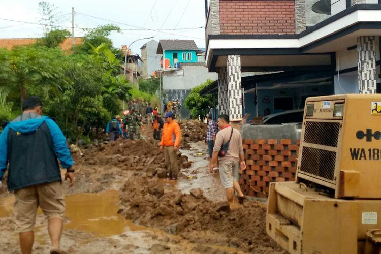 Tampak petugas gabungan dari sejumlah instansi membantu membersihkan material lumpur dan batuan yang terbawa banjir bandang yang disebabkan tanggul penahan aliran air sungai di sekitar Komplek Jatiendah Regency jebol diterjang.
