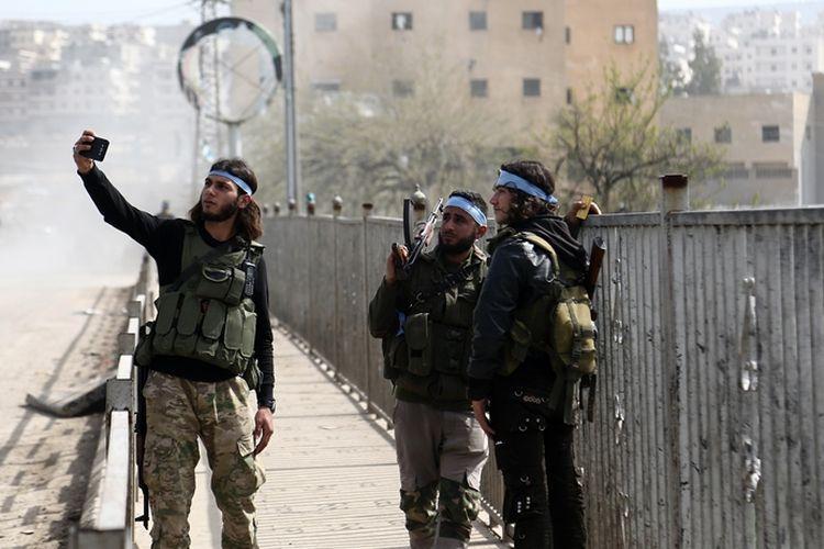 Anggota pasukan pembebas Suriah (FSA) yang didukung Turki melakukan swafoto bersama setelah mereka berhasil menguasai pusat Afrin, Minggu (18/3/2018).