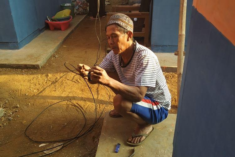 Seorang penyintas memassng instalasi listrik sendiri yang disambungkan ke jaringan listrik yang terdapat di hunian sementara (huntara) Nyalindung, Sukabuni, Jawa Barat, Selasa (3/9/2019).