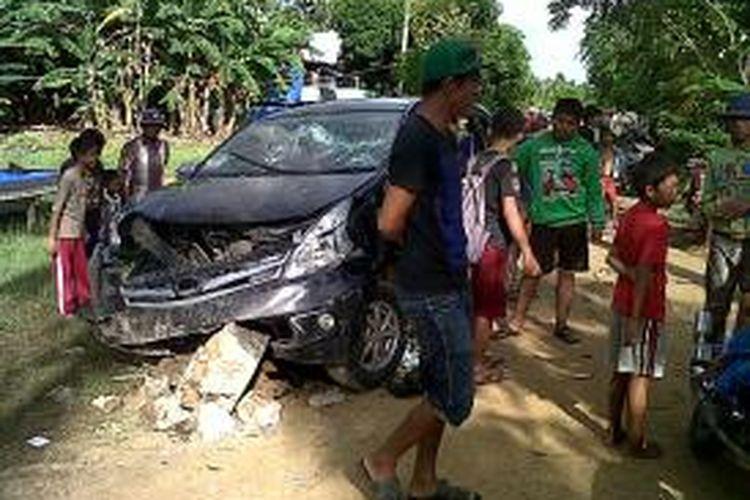 Minibus milik pelaku perampokan yang diamuk warga dan menewaskan seorang pelaku tengah menjadi tontonan warga Desa Labotto, Kecamatan Cenrana, Kabupaten Bone, Sulawesi Selatan. Rabu, (02/04/2014).