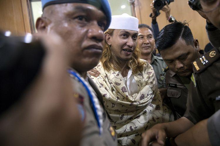 Tersangka kasus dugaan penganiayaan terhadap remaja Bahar bin Smith (tengah) dikawal petugas menuju ruang sidang sebelum menjalani sidang perdana di Pengadilan Negeri Bandung, Jawa Barat, Kamis (28/2/2019). Sidang perdana tersebut beragenda pembacaan dakwaan.