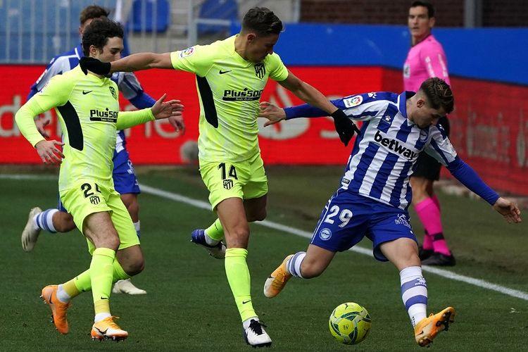 Pemain Atletico Madrid, Marcos Llorente dan Sime Vrsaljko, memburu bola yang dikuasai pilar Alaves, Borja Sainz, dalam laga Liga Spanyol 2020-2021 di Stadion Mendizorroza pada 3 Januari 2021.
