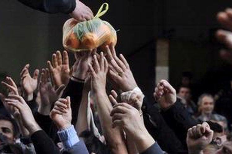 Para petani Yunani membagikan buah-buahan dan sayuran gratis sebagai bentuk protes atas rencana pemerintah menaikkan pajak produk pertanian.