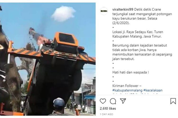 Tangkapan layar sebuah video yang menampilkan mobil crane terjungkir ke depan karena tak kuat angkat potongan pohon di Malang, Jawa Timur.