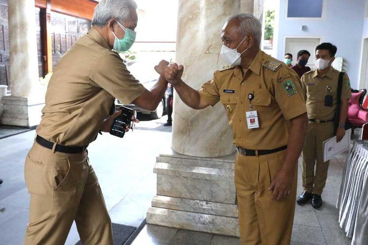 Gubernur Jawa Tengah Ganjar Pranowo disambut Plh Bupati Banjarnegara (kanan) saat kunjungan ke Banjarnegara, Senin (6/9/2021).