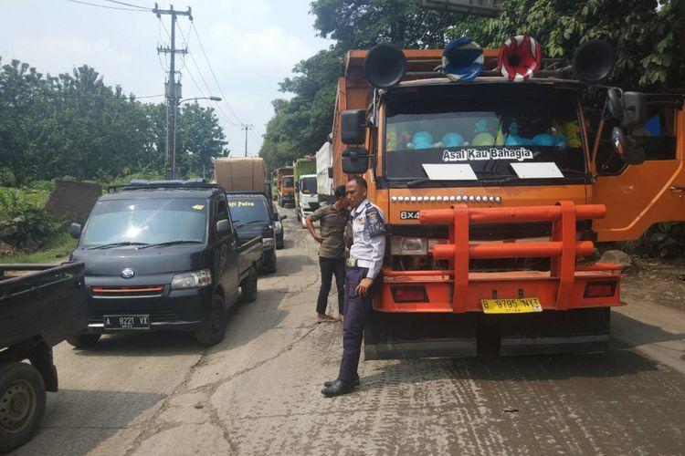 Petugas Dishub Kab. Tangerang menerapkan buka-tutup arus di Jalan Raya Parung untuk menghindari penumpukan kendaraan, Rabu (9/1/2019).