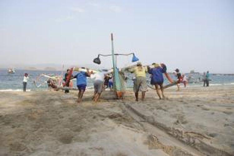 Para nelayan bahu membahu mendorong perahu menuju laut di Pantai Tanjung Papuma, Jember, Jawa Timur, Jumat (11/9/2015). Pantai Tanjung Papuma berada di pantai selatan Jawa Timur. Pantai Tanjung Papuma terletak sekitar 45 kilometer dari Stasiun Jember.