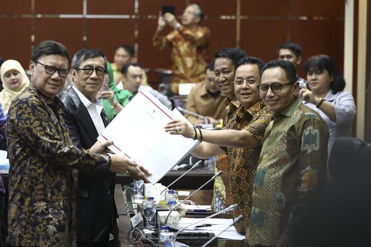 Menteri Dalam Negeri Tjahjo Kumolo (kiri bersama Menteri Hukum dan HAM Yasonna H Laoly (kanan) menyerahkan daftar inventaris masalah saat rapat kerja bersama Badan Legislasi DPR di komplek parlemen, Senayan, Jakarta, Kamis (12/9/2019). Rapat membahas revisi UU MD3 dan perubahan kedua atas UU nomor 30 tahun 2002 tentang KPK. ANTARA FOTO/Tyaga Anandra/Lmo/pd.