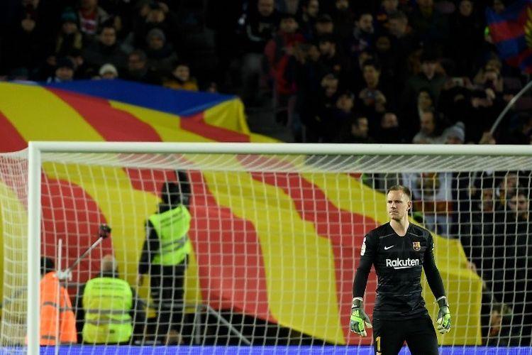 Kiper Barcelona, Marc-Andre Ter Stegen berdiri di atas lapangan ketika penggemar Barcelona membentangkan bendera pro-kemerdekaan Catalan di tribun selama pertandingan sepak bola liga Spanyol antara FC Barcelona dan Granada FC di stadion Camp Nou di Barcelona pada 19 Januari 2020.