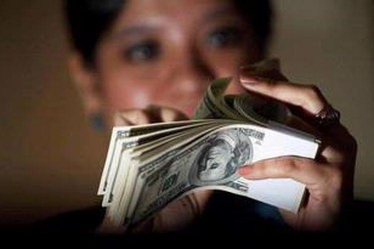 Petugas kasir menghitung uang Dollar Amerika di Kantor BNI Pusat di Jakarta.