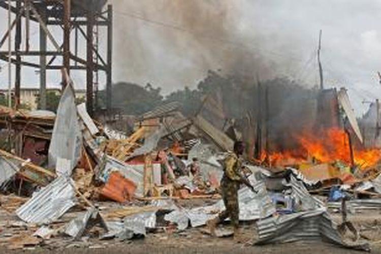 Seorang anggota militer Somalia berjalan melewati puing-puing akibat ledakan bom bunuh diri yang menyerang konvoi pasukan Uni Afrika di Mogadishu.