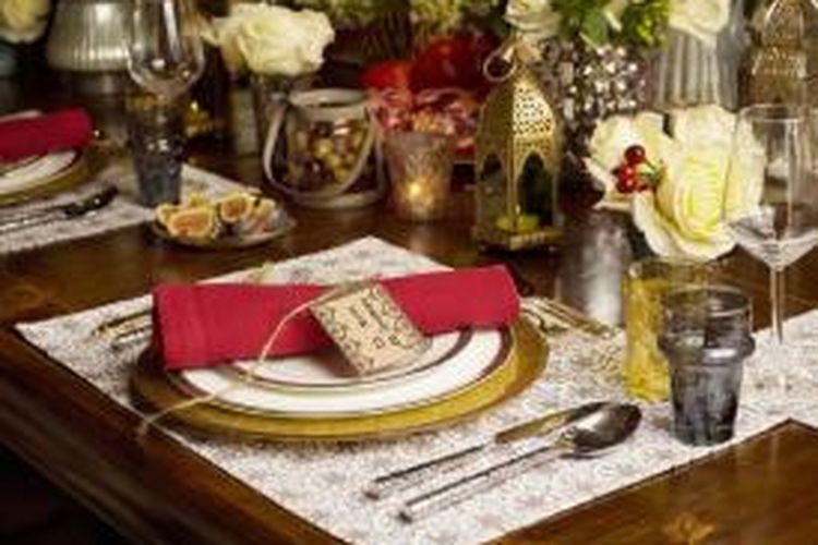 Sentuhan dekorasi Maroko lewat lentera-lentera mungil berwarna emas dan vas modern bernuansa senada dilengkapi dengan mawar-mawar putih. Sementara itu, serbet berwarna merah di atas setiap piring juga punya andil menyempurnakan tampilan meja makan tersebut.