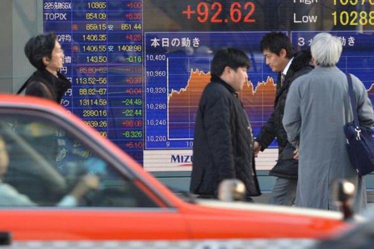 Ilustrasi: Para pejalan kaki melewati sebuah papan elektronik yang memajang perkembangan di bursa saham Nikkei, Jepang.