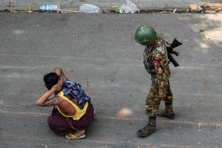 Seorang tentara berdiri di belakang seorang pria yang ditahan, dalam demonstrasi menentang kudeta di Mandalay, Myanmar, pada 3 Maret 2021.