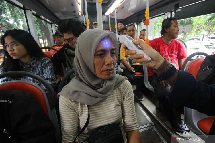 Petugas memeriksa suhu tubuh penumpang Bus Suroboyo, layanan bus Kota Surabaya, di Terminal Purbaya, Sidoarjo, Jawa Timur, Kamis (5/4/2020). ANTARA FOTO/Didik Suhartono