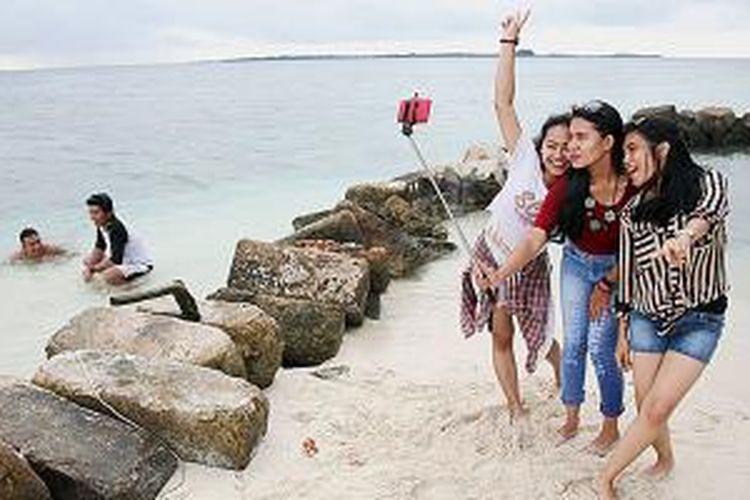 Wisatawan berfoto selfie di Pulau Genteng Kecil, Kelurahan Pulau Harapan, Kecamatan Kepulauan Seribu Utara, Kepulauan Seribu, Minggu (25/1/2015). Hamparan pasir putih di pantai pulau-pulau kecil di kepulauan seribu menjadi daya tarik wisata.