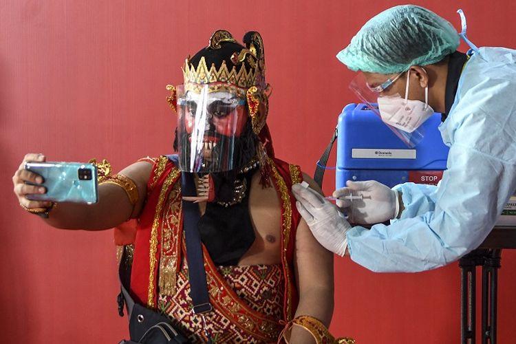 Seorang seniman dengan kostum pewayangan disuntik dosis pertama vaksin COVID-19 saat vaksinasi massal bagi seniman dan budayawan di Galeri Nasional, Jakarta, Senin (19/4/2021). Sekitar 500 seniman dan budayawan di Jabodetabek menerima vaksin guna menekan penularan COVID-19 agar sektor ekonomi kreatif  nasional dapat segera pulih dan bangkit. ANTARA FOTO/M Risyal Hidayat/hp.