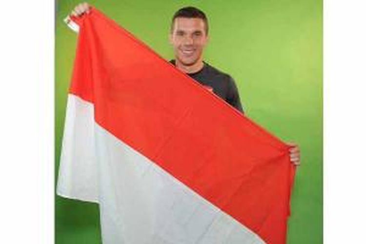 Striker Arsenal, Lukas Podolski, mengangkat bendera Merah-Putih.