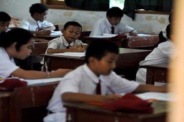 Murid SDN Kemiri Muka 02, Beji, Depok, mengerjakan soal Bahasa Indoensia pada hari pertama ujian nasional di sekolah mereka, Senin (6/5/2013). Pelaksanaan ujian nasional di sekolah ini lancar yang diikuti 19 siswa.
