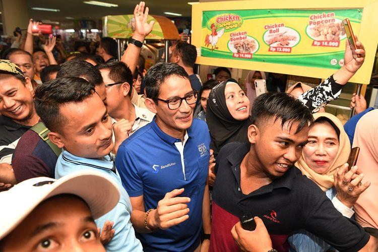Calon Wakil Presiden Sandiaga Uno (tengah) menyapa pengunjung dan pedagang ketika berkunjung ke Pusat Grosir Surabaya (PGS), Surabaya, Jawa TImur, Minggu (21/10/2018). Kunjungan tersebut dalam rangka meyapa para pedagang sekaligus meninjau perekonomian di pusat perbelanjaan itu. ANTARA FOTO/Zabur Karuru/ama