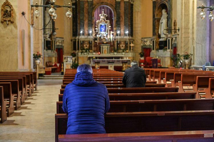 Sejumlah orang berdoa di gereja Santa Maria delle Grazie alle Fornaci, di Distrik Aurelio di sentral Roma, pada 15 Maret 2020. Peristiwa ini terjadi di tengah lockdown yang diterapkan Italia guna memerangi virus corona.