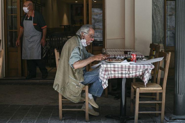 Seorang pelanggan sedang makan di salah satu restoran di Yunani yang sudah mulai dibuka kembali usai lockdown.